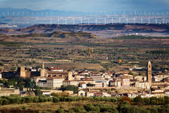Old village, plain terrain and modern wind turbines Stock Photography