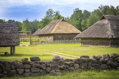 Old village and stone fence in front, Žemaitija region, Lithuania royalty free stock image