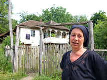 Old village woman in front of her rural, traditional house Stock Images