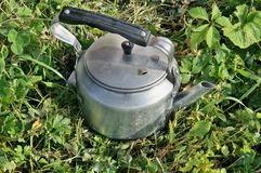 Old vintage aluminum electric kettle on a green rustic lawn Stock Images