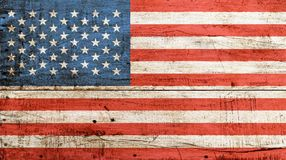 Old vintage American US flag over white wood. Old grunge vintage American US national flag over background of white painted wooden planks board Royalty Free Stock Photos