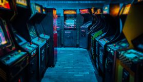 Old Vintage Arcade Video Games in an empty dark gaming room with blue light with glowing displays stock photography