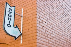 Old Vintage Arrow Studio Sign Pointing on an Urban Brick Wall. A vintage studio arrow sign pointing to a brick building along a city alleyway stock photos