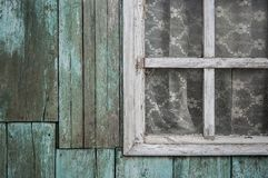 Old vintage barn wall with wooden window. Simple old window with shutters on wooden wall stock photography