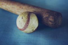 Old vintage baseball and bat against blue texture background. Wooden bat showing detail in grain laying beside an old rough and rugged baseball.  Ball has Stock Image