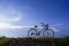 Old vintage bicycle with dramatic blue sky at background. Royalty Free Stock Photography