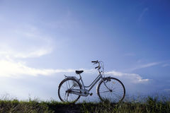Old vintage bicycle with dramatic blue sky at background. Stock Image