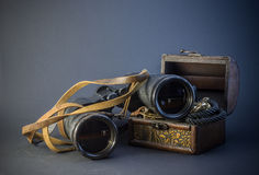 Old vintage Binoculars with treasure. Black background. Close up. Stock Photography