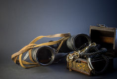 Old vintage Binoculars with treasure. Black background. Close up. Royalty Free Stock Photo