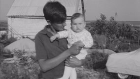 Old vintage black and white film young man holding baby in hands at village. Old vintage black and white film stock video footage