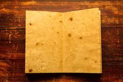 Old vintage book on the aged wooden background. Two clean sheet of paper. Stock Image