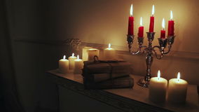 Old vintage books with candles in candlestick. stock video