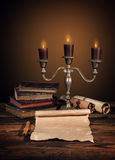 Old vintage books with candles in candlestick Stock Photos