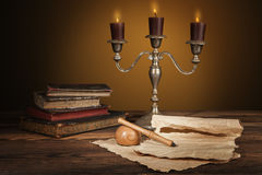 Old vintage books with candles in candlestick Stock Image
