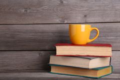 Old vintage books and cup on grey wooden table royalty free stock image