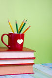 Old vintage books and cup with heart shape on wooden table Royalty Free Stock Photos