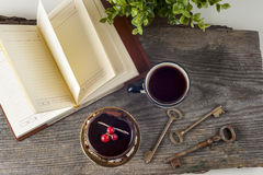Old vintage books, cup of tea, cake and keys on rustic wooden table royalty free stock photos