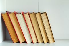 Old books are on the shelf. Old vintage books standing upright on a shelf Stock Image