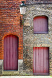 Old vintage brick wall with red wooden doors and windows Royalty Free Stock Photography