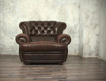 Old vintage brown leather chair. In empty room Royalty Free Stock Images