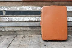 Old vintage brown suitcase on wooden wall. Old and broken vintage brown suitcase on the wooden wall Stock Images