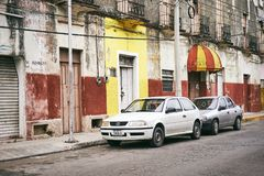 Merida / Yucatan, Mexico - June 1, 2015: The cars parking infront of the old buiding in contrast with bright yellow color wall in. The old, vintage building with royalty free stock photography
