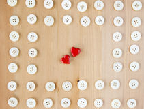 Old vintage buttons frame border with two red wooden hearts in the middle. Sewing, hobby, lifestyle concept Royalty Free Stock Photo