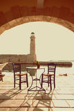 Old vintage cafe and lighthouse on the sea Rethymnon Royalty Free Stock Image
