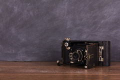Old vintage camera against a blackboard background Stock Photos