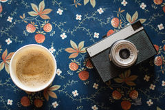 Old vintage camera with a cup of coffee on  fabric background. Old vintage camera with a cup of coffee on vintage fabric background Stock Photos