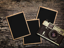 Old vintage camera and photos on a wooden background Royalty Free Stock Photos