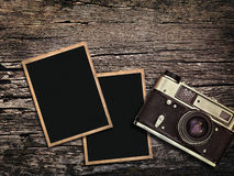 Old vintage camera and photos on a wooden background Royalty Free Stock Photo