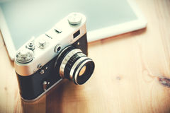 Old vintage camera. With a tablet on a wooden table royalty free stock images