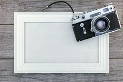 Old vintage camera and white empty frame on wooden background to Stock Photos