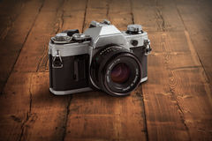 Old vintage camera on a wood table top Royalty Free Stock Images