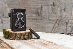 Old vintage camera on wooden stand, wooden background, retro theme, auctions and hobbies. Old vintage camera on wooden stand, wooden background, retro theme Stock Image