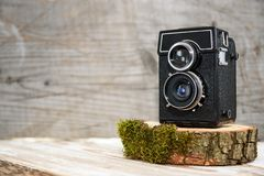 Old vintage camera on wooden stand, wooden background, retro theme, auctions and hobbies. Old vintage camera on wooden stand, wooden background, retro theme Stock Photo