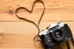 Old vintage camera on a wooden table. Heart shape royalty free stock images