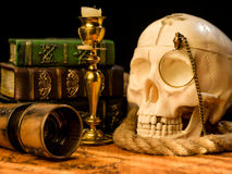 Old vintage candlestick, skull and spyglass on ancient world map Stock Photos