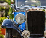 Old vintage car. Antique car headlight and grille of an old retro vintage blue classic car. Old vintage car. Front view. Shallow depth of field. Selective focus Royalty Free Stock Images