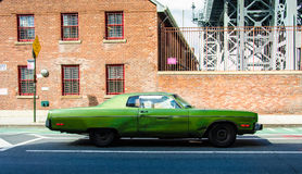Old vintage car on a street in Brooklyn (New York). With adobe building in the background Royalty Free Stock Images
