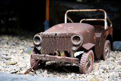 Old vintage car toy with rusty surface parking on the gravel stone floor. Old vintage car toy with rusty surface parking on the gravel stone floor, selective stock images