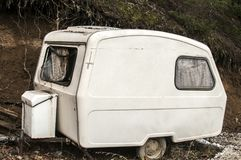 77a92c6d3d7f0b Old abandoned weathered small white vintage caravan royalty free stock image