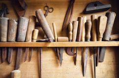 Old vintage carpenter tools. Hanging from the wall of a dusty workshop royalty free stock images