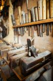 Old vintage carpenter tools. On the wall and bench of a dusty workshop royalty free stock photos
