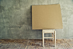 Old vintage chair and empty cardboard Royalty Free Stock Photography