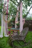 Old vintage chair with romantic picture frames and flowers on green grass stock photo