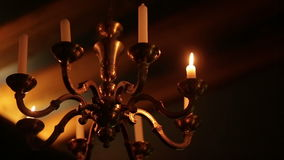 Old vintage chandelier with candles burning in the dark stock footage