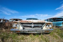 Old Vintage Chrysler 300 Car, Junk Yard. An old vintage classic Chrysler 300 sits in rust in a junk yard. The automobile car is rusted and a wreck Stock Image