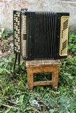 Old vintage classic musical instrument accordion on a shabby wooden stool in the courtyard of a village house against a white wall stock photography